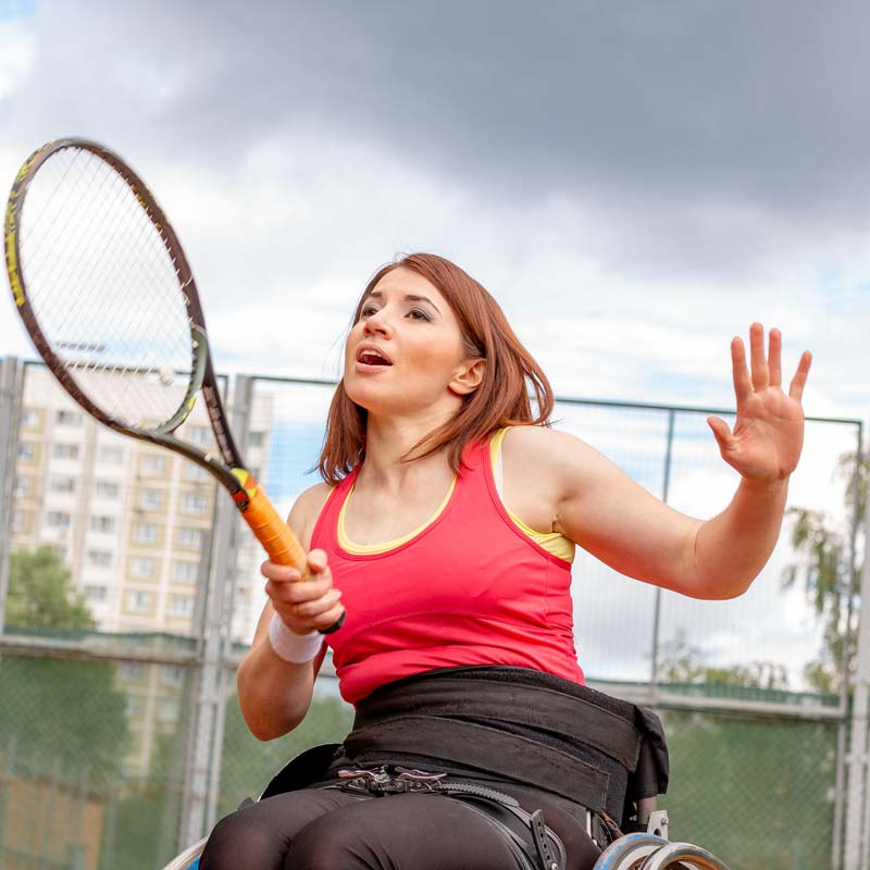 woman playing tennis in wheelchair